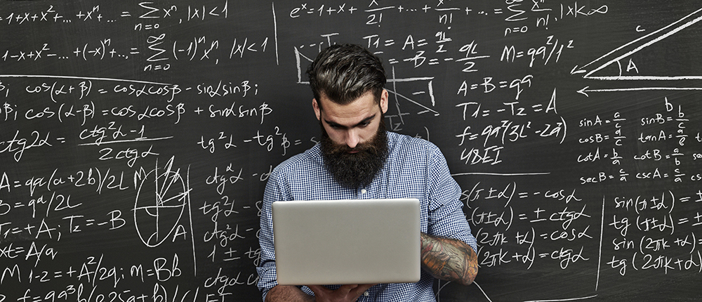 Tattoed man working with laptop near chalkboard with formulas